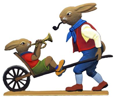 Der Osterhase schiebt ein Hasenkind auf einer Schubkarre